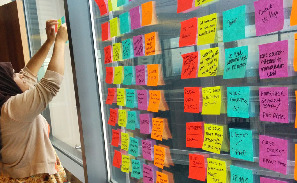 Image: Woman working with brightly colored sticky notes during project discovery phase